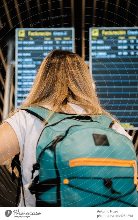 Rear view of a young blonde woman looking at the airport flight information screens. rear view display bag female time passenger vacation traveler journey trip