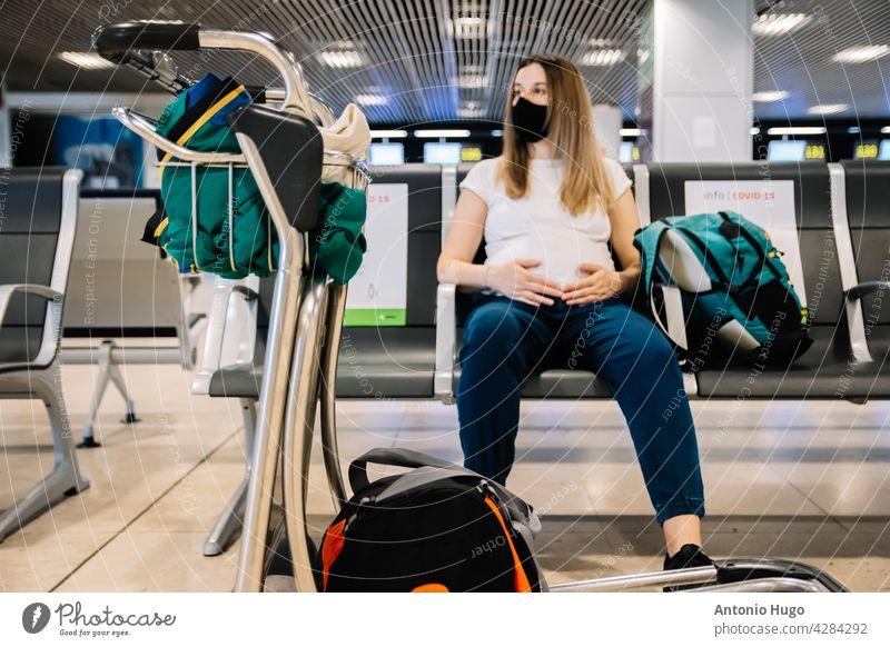 Pregnant woman with face mask sitting while waiting for her flight departure at the airport. Trolley full of luggage. trolley pregnant fly mother female journey