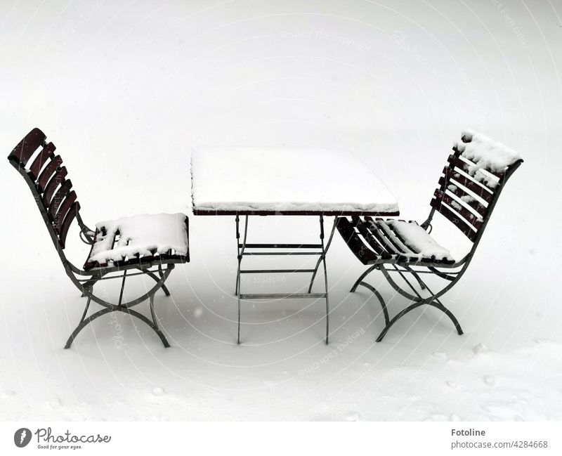 A cozy spot in the snow. 2 snow-covered chairs and a table are waiting for guests who need a little cooling down. Snow Winter Light Cold White Ice Frost Frozen