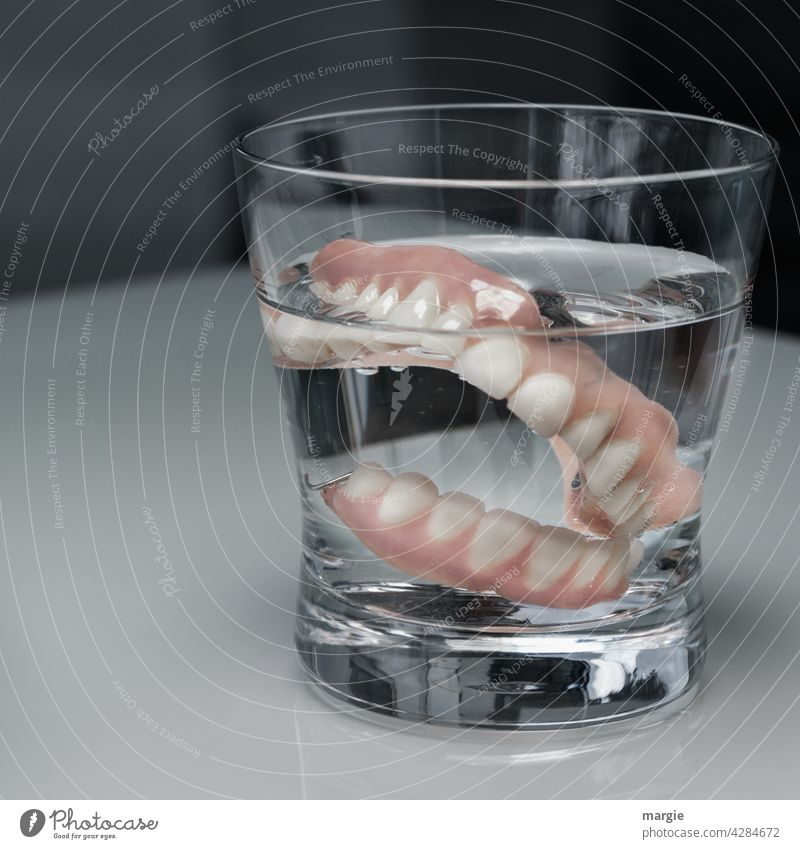 Dentures (teeth) in a glass of water Dental implant Set of teeth Dentistry Healthy Teeth Mouth care Close-up Laboratory dental health senior citizens age