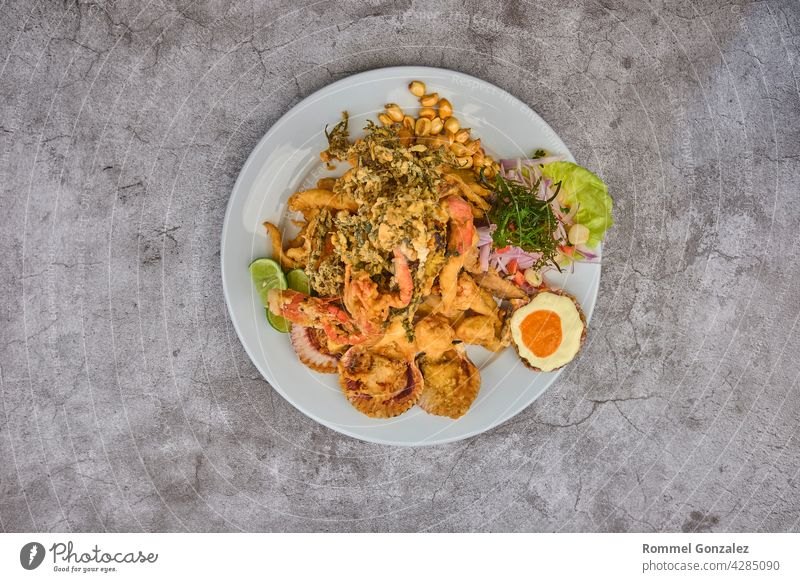 Peruvian food: Jalea de pescado or fish cracklings with fried cassava and onion salad with chili, served on a white plate. Fried seafood peru meal traditional