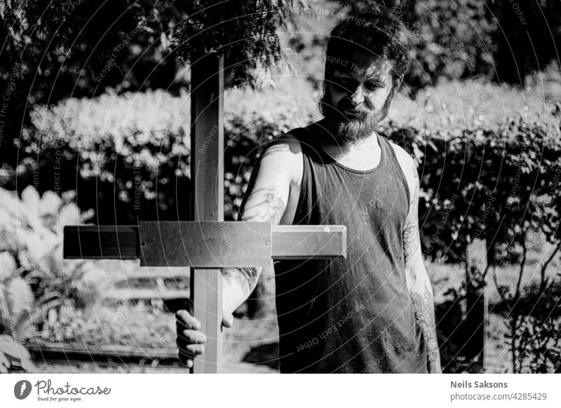 male with tattoos and beard holding wooden christian cross in cemetery. portrait tattoed catholic religion Religion and faith Crucifix Christian cross