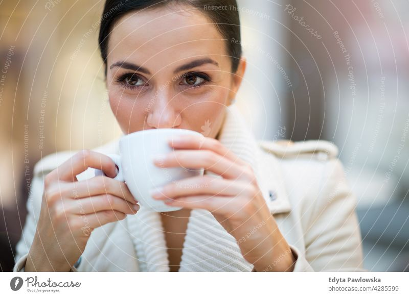 Young woman drinking coffee in cafe beverage enjoying lifestyle young adult people one person casual caucasian positive carefree sitting happy smile smiling