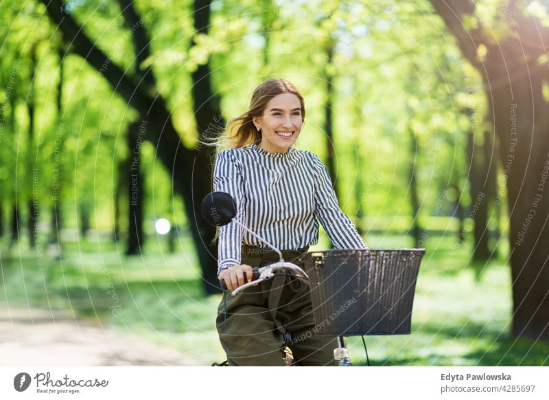 Young woman cycling through the park green trees nature freshness enjoying lifestyle young adult people casual caucasian positive happy smiling female