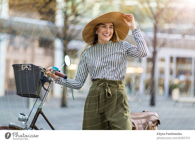 Young woman standing with her bicycle in the city straw hat holiday vacation fashion park green trees nature freshness enjoying lifestyle young adult people