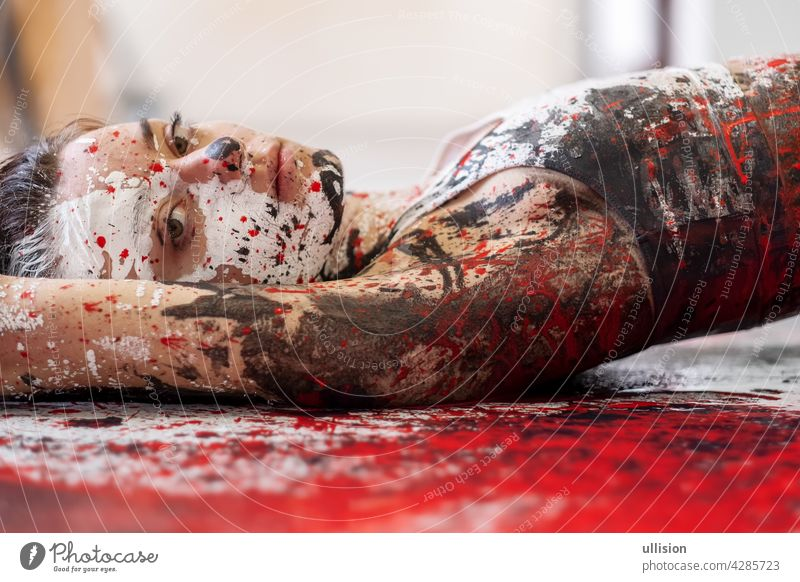 young and sexy Woman in underwear, sportswear, artistically abstract painted with white, red and black paint, lying on the colorful painted floor in the studio, copy space.
