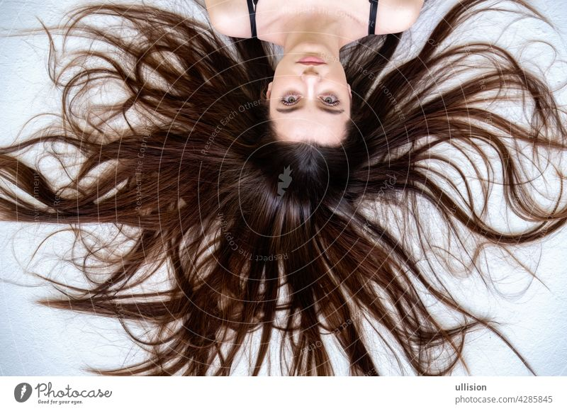 Beautiful young woman lying on the white background with long widespread sprawled hair brown fashion haircare vogue brunette wave silky styling sexy cute beauty
