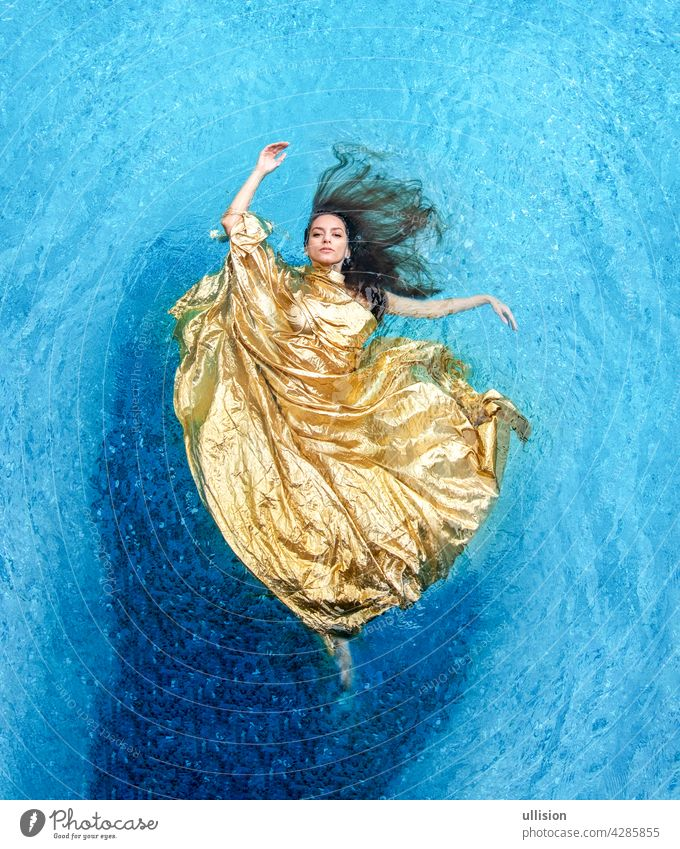 Top view of a beautiful young sexy woman in golden dress, evening dress, towel floats weightlessly elegantly swimming in the pool water cloth mermaid blue