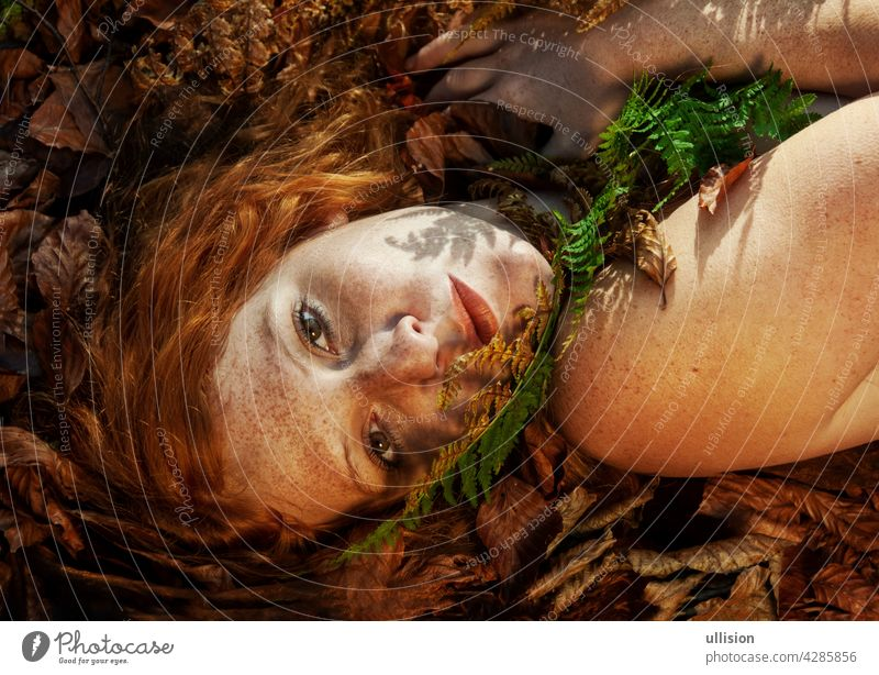 Beautiful sexy lovely young redhead girl lying on red golden autumn leaves, with a frond of fern on his chin, in the forest, with friendly seductive smile in the face