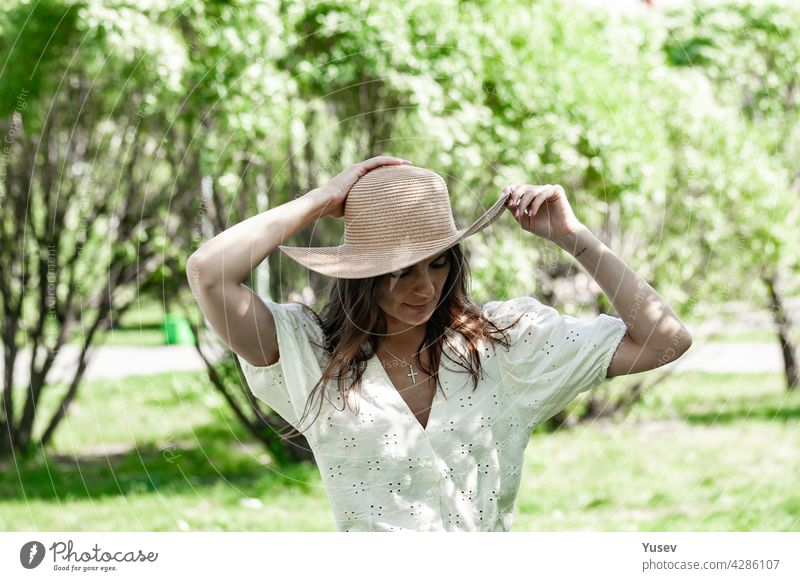 Young beautiful happy woman in fashionable straw hat. A brunette female in a white shirt stand outdoor and holds her hat with hands. Blooming spring apple tree park background. Sunny summer day