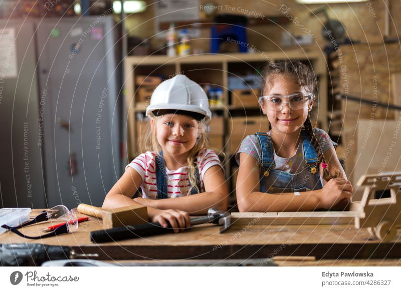 Two young girls doing woodwork in a workshop working people child children kid kids girl power Skill craft Garage Hobby Lifestyle tools Concentration Creativity