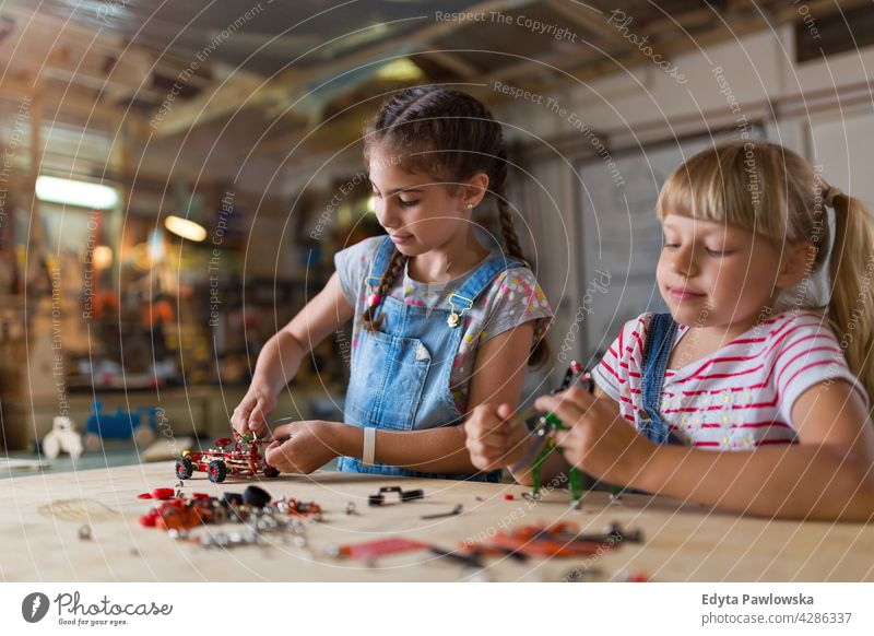 Small girls building toy construction machine workshop learning people child children kid kids girl power Skill craft Garage Hobby Lifestyle tools Concentration
