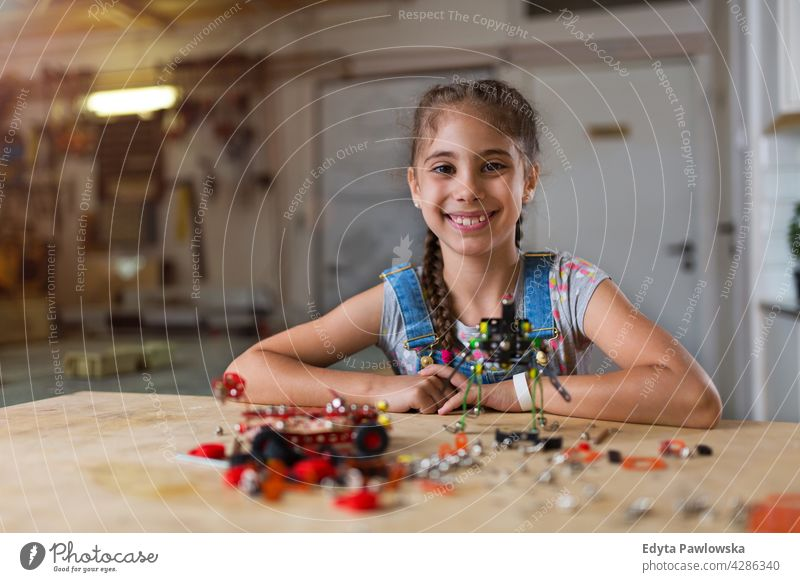 Small girl making a robot workshop learning people child children kid kids girl power Skill craft Garage Hobby Lifestyle tools Concentration Creativity