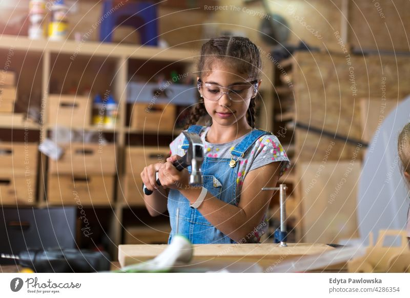Young girl doing woodwork in a workshop working people child children kid kids girl power Skill craft Garage Hobby Lifestyle tools Concentration Creativity