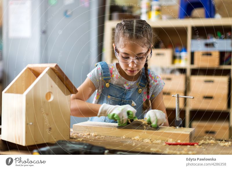 Girl building birdhouse in garage workshop working people child children kid kids girl girl power Skill craft Garage Hobby Lifestyle tools Concentration