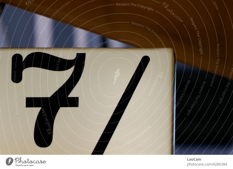 Black 7 and black line on white background sieving number figures digit Digits and numbers dash strokes Signs and labeling sign White Exterior shot Characters