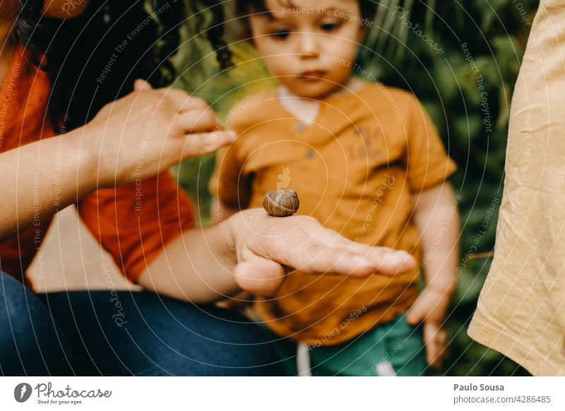 Mother shows snail to children motherhood Child Caucasian 1 - 3 years Snail Parents Cute Love Together Family & Relations togetherness people Infancy care Happy