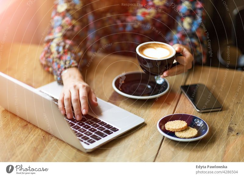 Woman with laptop in cafe breakfast desk espresso morning tea closeup people woman young adult Caucasian one person day coffee shop sitting table office