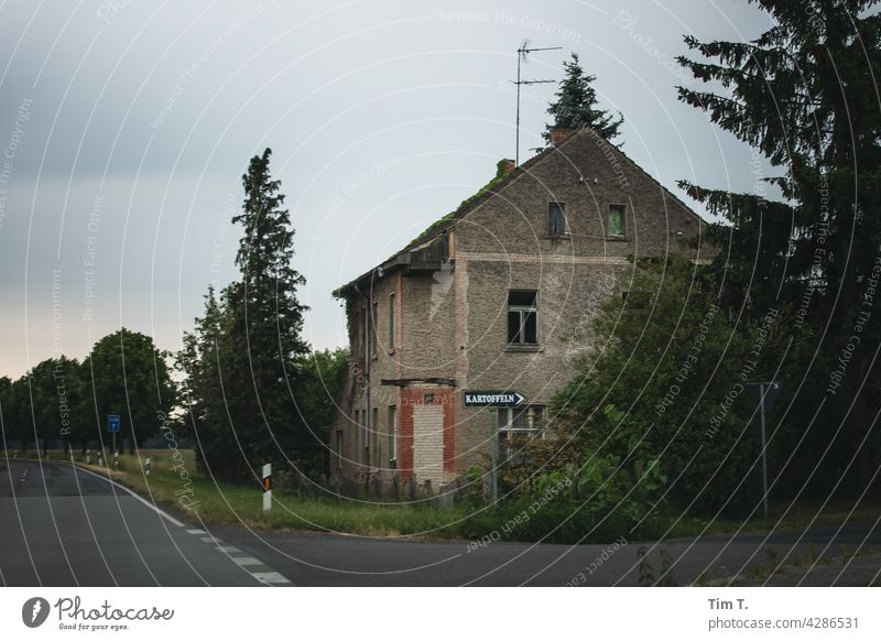 an old house on a Brandenburg country road . A sign in front of it with the inscription potatoes shows the way. Potatoes Country road Street Tree Deserted