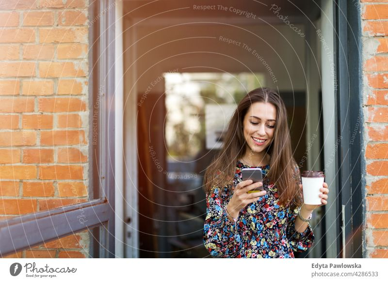 Young woman standing in front of a cafe urban Street City stylish Coffee to go people Woman young adult more adult Easygoing Attractive Smiling Happy Caucasian
