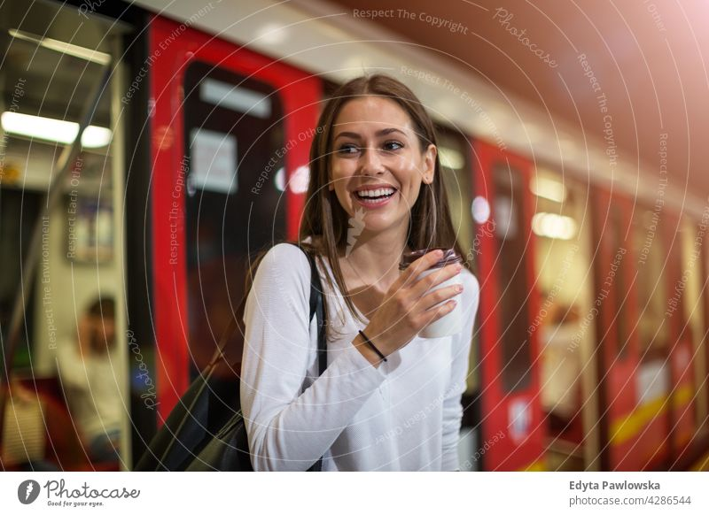 Young woman at subway station people young adult casual attractive female smiling happy Caucasian toothy enjoying one person beautiful portrait positivity