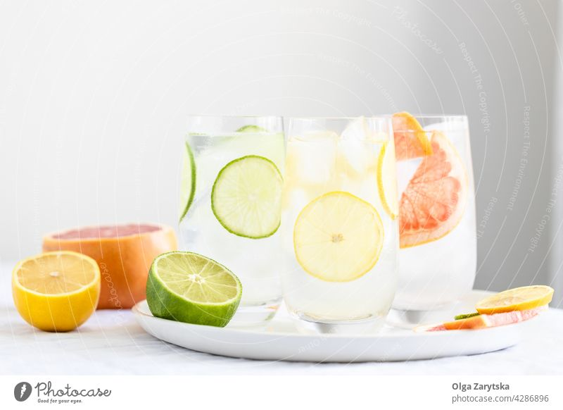 Three glasses with cold citrus water. drink lemonade ice grapefruit lime summer refreshment perspiration set beverage three white tablecloth minimal cocktail