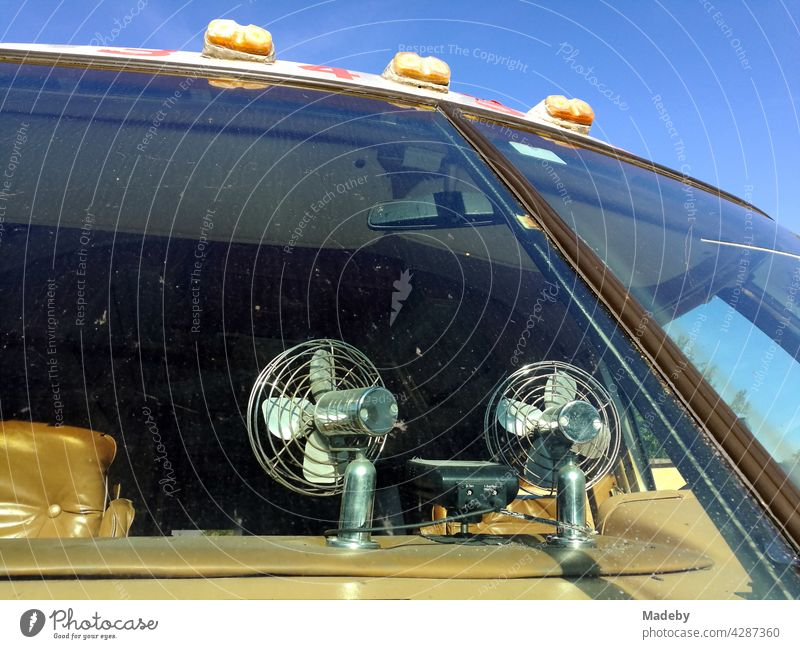 Fans on the dashboard of a classic american camper van of the luxury class in front of a blue sky at sunshine in Detmold in East Westphalia-Lippe, Germany.