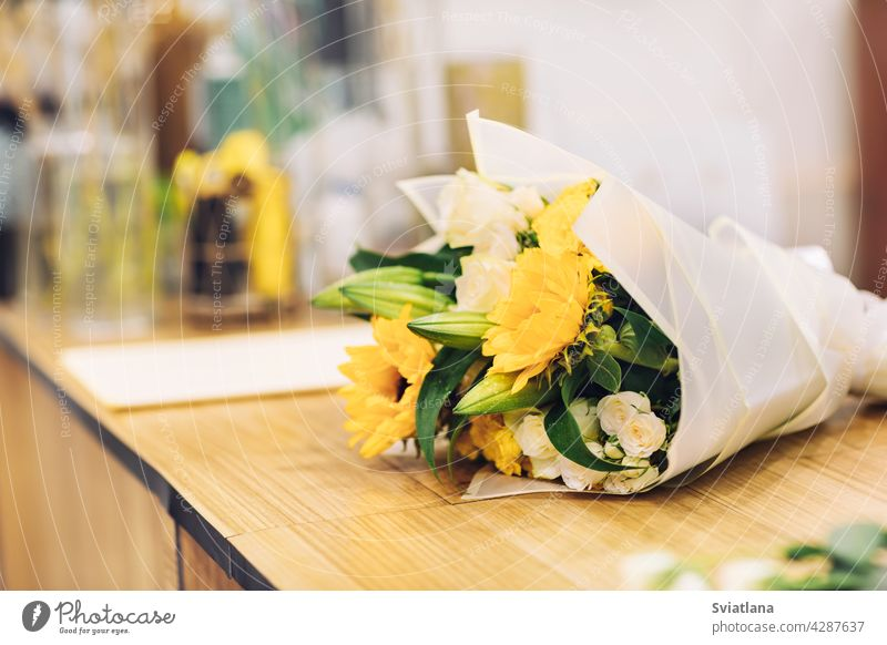 A beautiful bouquet of bright mixed flowers lies on a wooden table, the work of a florist in a flower shop bouquet of flowers flowers workshop gift yellow color