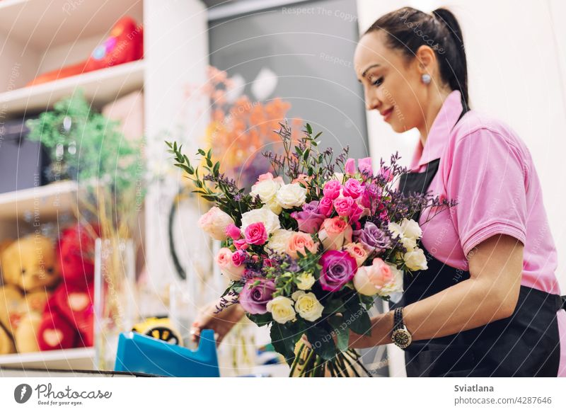 A florist girl in a flower shop makes a bouquet for the holiday. Family flower business, beautiful flower arrangement. flower composition pink roses