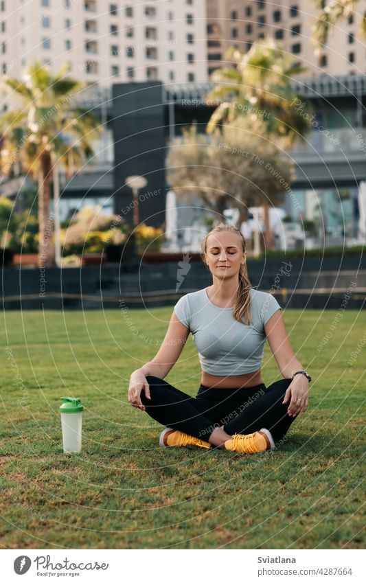 A young woman sits in the lotus position on the lawn in the park next to the house and meditates after a workout. Sports, fitness, yoga. Healthy Lifestyle Concept