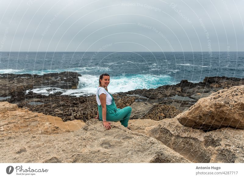 Portrait of a pregnant woman sitting on a rock. Dressed in a green dungarees observing the force of the sea. mom maternity expecting waves breaking volcanic
