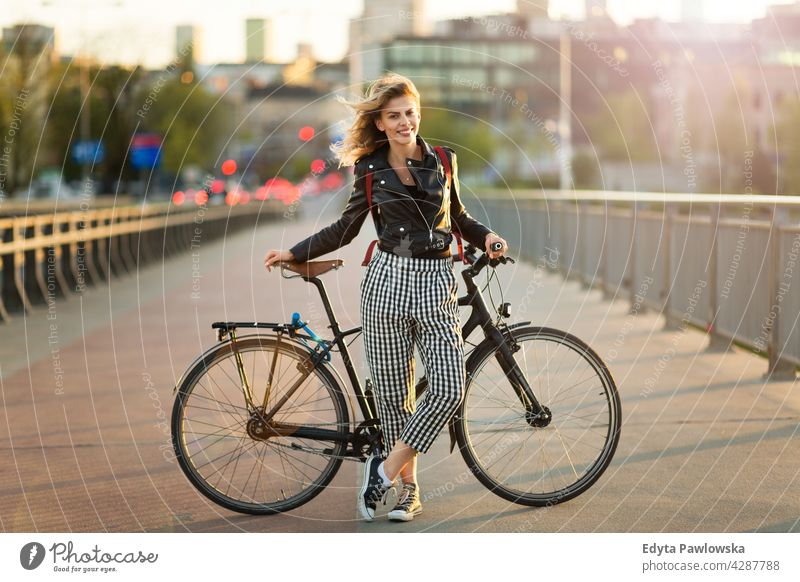 Attractive young woman standing with her bicycle in the city enjoying lifestyle adult people casual caucasian positive happy smiling female attractive beautiful