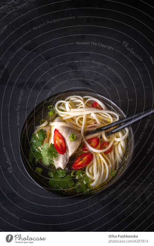Asian soup and chopsticks with copy space on black above scallions close-up soup bowl vertical chicken stylish surface stone textured healthy food japanese
