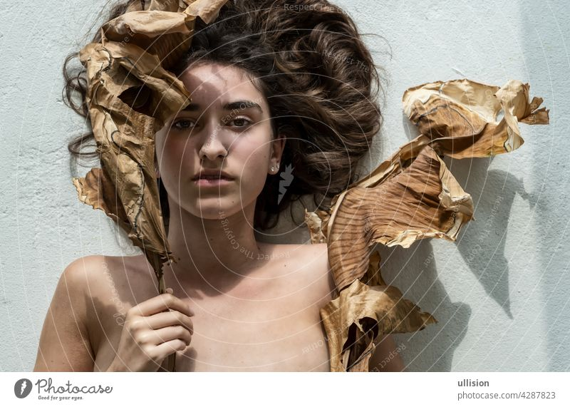 Portrait of a young sexy woman with brown hair artfully decorated between leaves of dry, withered banana tree looking like an art nouveau girl, copy space.