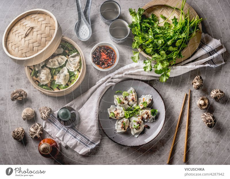 Asian food concept with homemade dumplings on plates and in steamer, fine shiitake, traditional sauces and crockery. White kitchen cloth on grey concrete background. Top view
