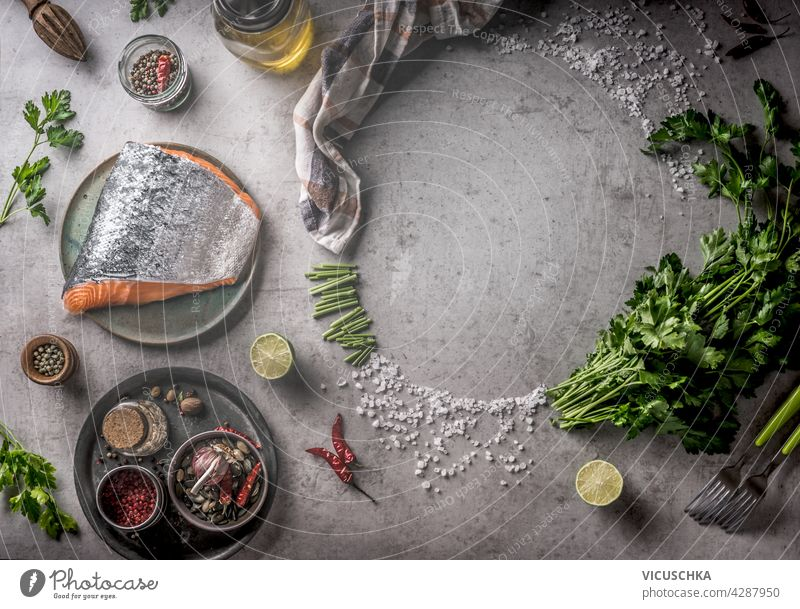Fresh raw salmon with frame of spices, oil, fresh herbs and lemon on grey concrete background. Cooking preparation with fresh ingredients at home. Equipment: fork, bowls and kitchen cloth. Top view