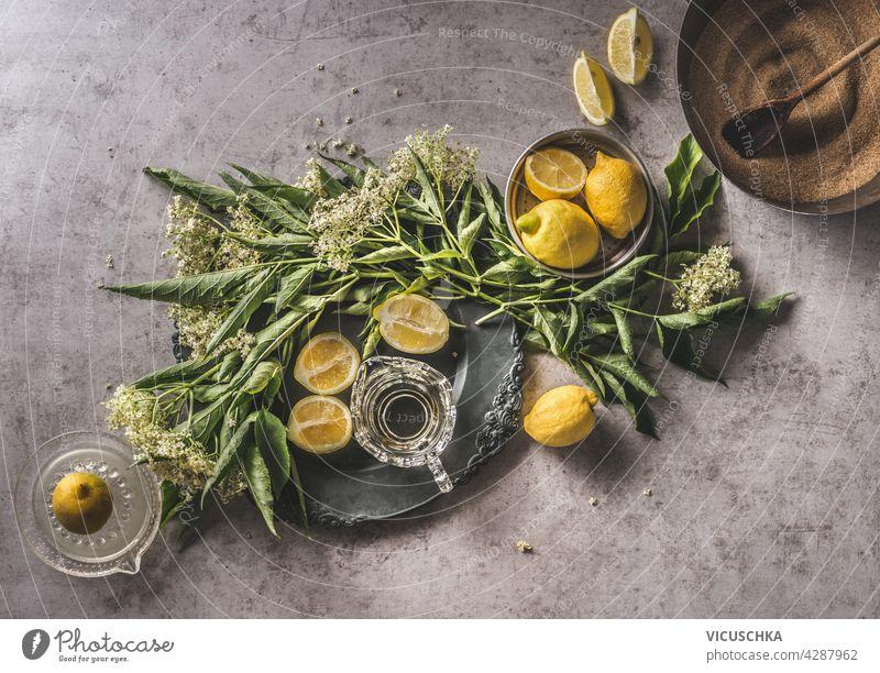 Homemade elder flower syrup with lemons, sugar, fresh lemon juice. Bundle of elder on decorated plate, kitchen equipment, dark concrete background. Top view