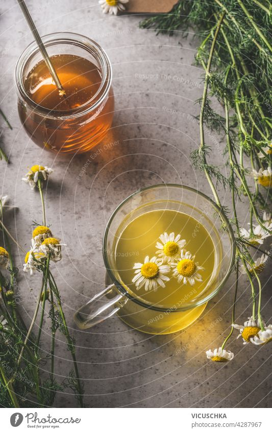 Honey and fresh brewed tea with organic herbs on dark concrete background. Natural treatment. Top view honey natural autumn theme top view copy space product