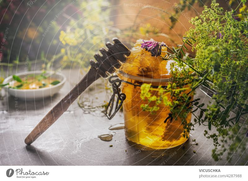 Closeup of jar with honey and honey spoon and wild flowers. Bowl with honey in background. Natural food concept. Dark concrete background. Front view. closeup