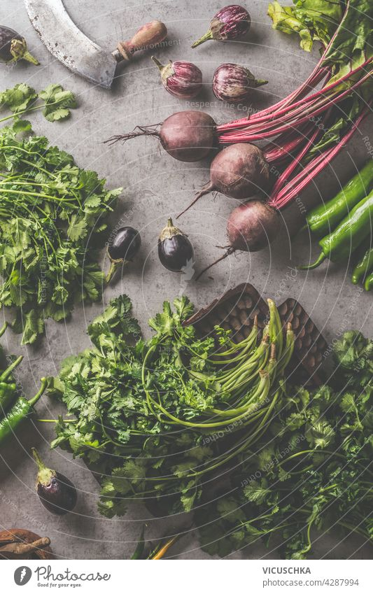 Fresh bundle of beetroot and herbs. Vegetables and vintage kitchen utensils on dark concrete background. Cooking preparation with fresh vegetables. Healthy food concept. Top view