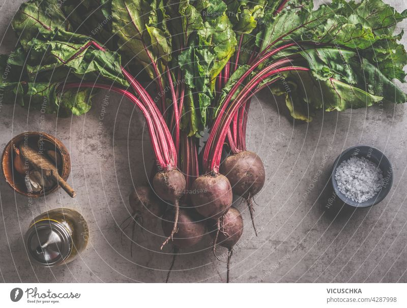 Fresh bundle of beetroot with greens leaves and cooking ingredients: olives oil, salt and garlic on dark concrete background.  organic vegetables. Healthy food concept. Top view