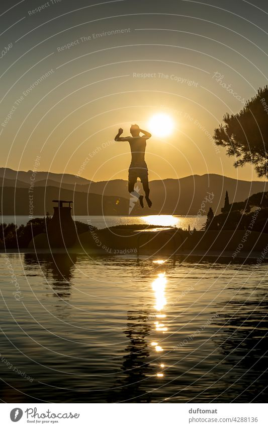 Teen jumps from diving board into the water in the evening Evening Sunset pool Boy (child) teenager Springboard Back-light Backlight shot Water Swimming pool