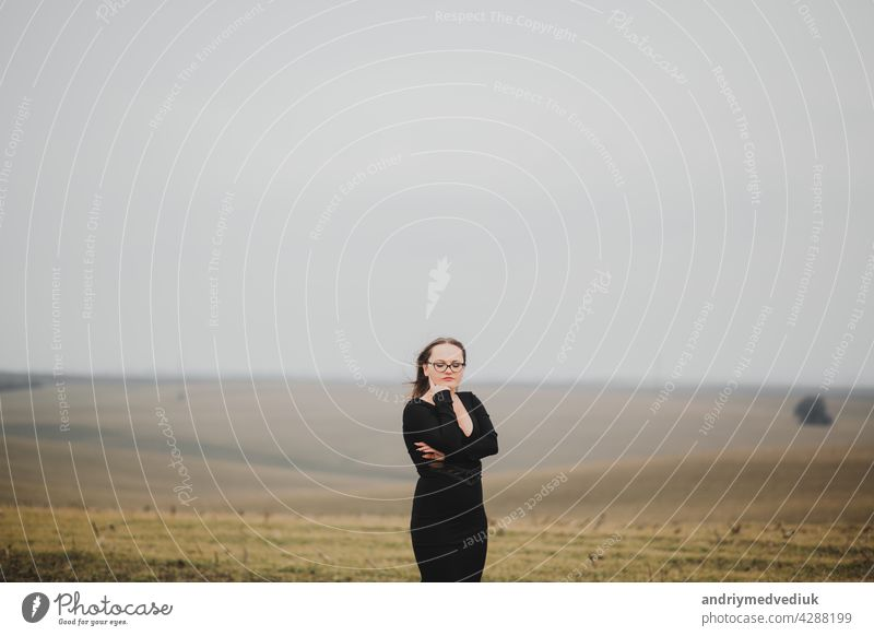 Young girl 20-25 years old in glasses and a black dress posing on a field background woman young outdoor beauty fashionable pose nature model romantic portrait