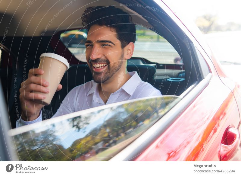 Businessman drinking coffee in car. businessman travel lifestyle taxi professional transportation vehicle backseat closeup to go auto stylish elegant young hot