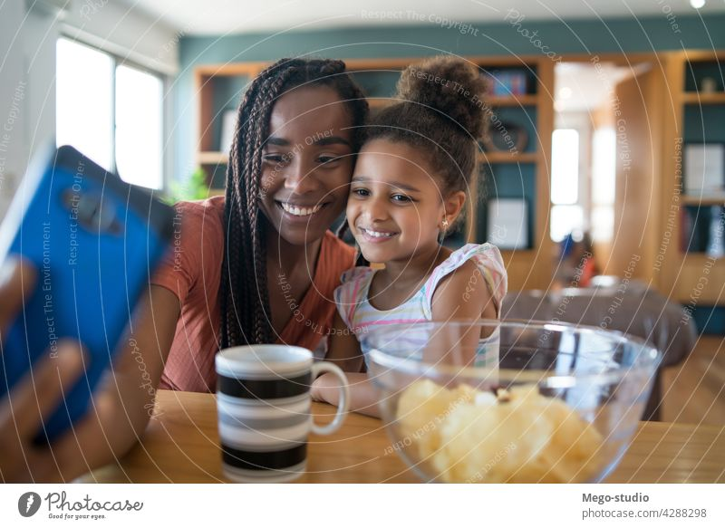 Mother and daughter taking selfie with phone. mother monoparental home lifestyle family single parent indoor mobile phone parenting relationship mom cute