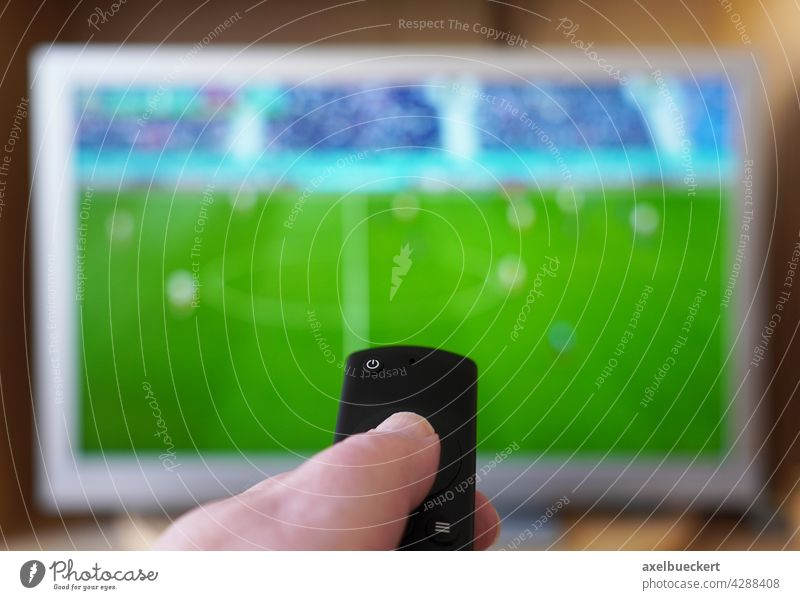 hand pointing remote control at tv with soccer or football match television watch spectator fan viewer thumb push button live watching tournament media finger