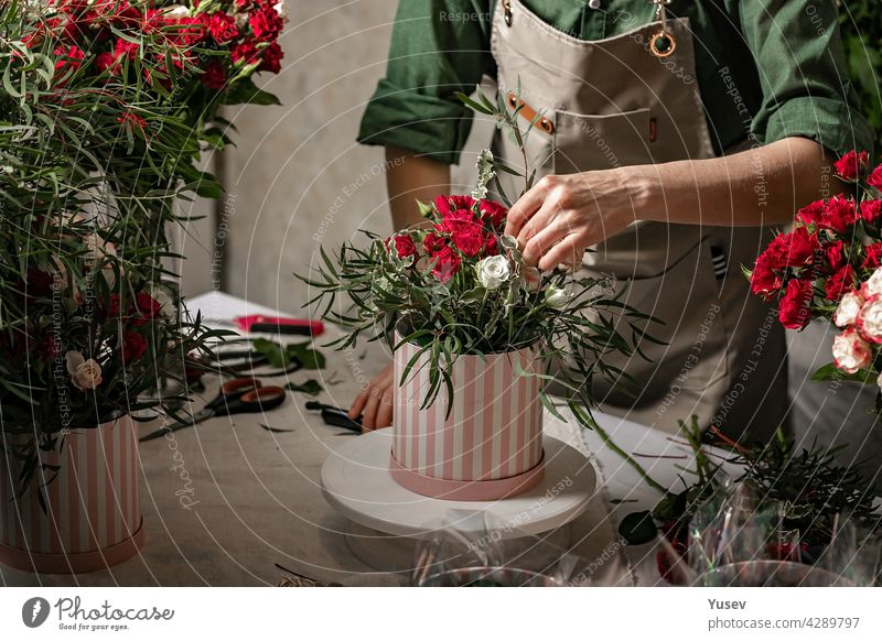 Florist make gift bouquets in hat boxes. Graceful female hands make a beautiful bouquet. Florist workplace. Small business concept. Front view. Flowers and accessories