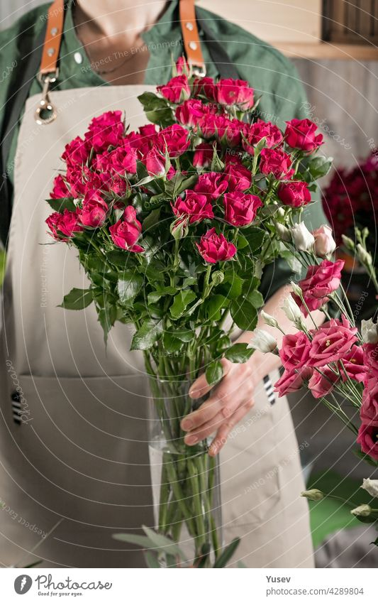 A florist woman in an apron holds a vase of roses. People at work. Florist workplace. Flower shop. Small business concept. Close-up. Vertical shot beautiful