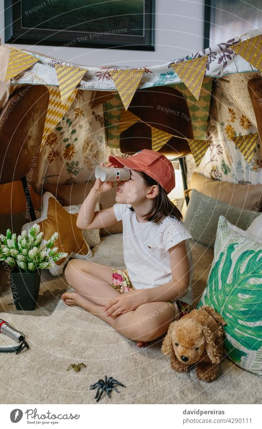 Girl playing with cardboard binoculars while camping at home happy girl observing vacation diy toys tent lockdown smiling coronavirus carton toilet paper tubes
