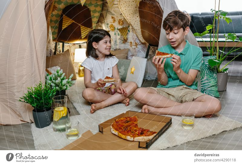 Children eating pizza and lemonade while camping at home children happy tent brother dinner lunch enjoy cheerful cute holiday food fun smiling homemade drink